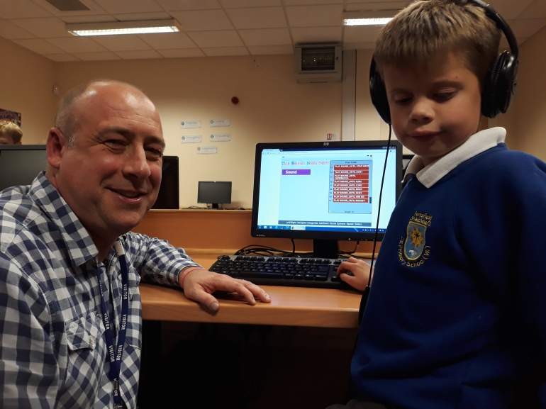A man and a boy in front of a computer