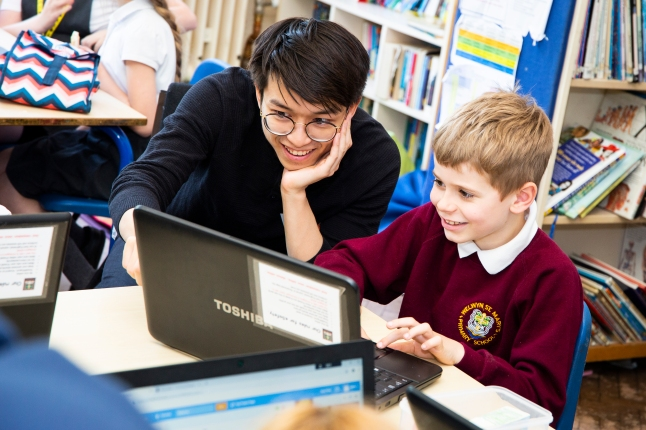Code Club volunteer from Tesco  supporting male club member with Scratch project.