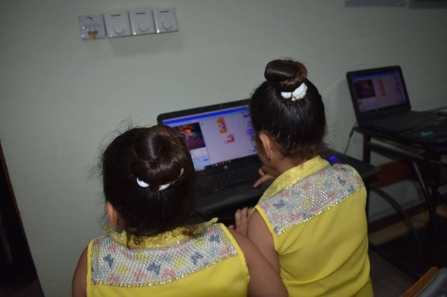 Two young girls dressed in yellow working at a computer.