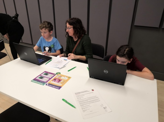 Angela with her two children sat at a desk look at a laptop.