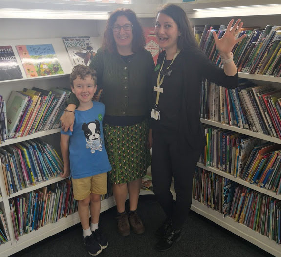 Angela and Anita and Angela's son stood in front of a book case.