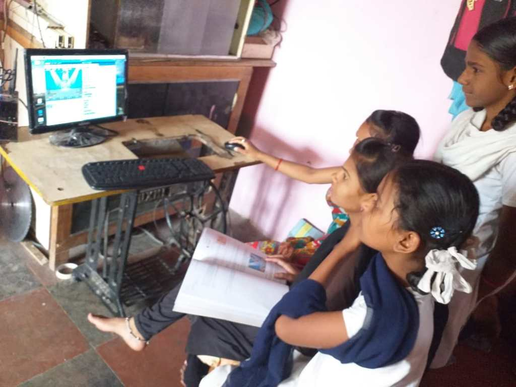Four girls gathered around a monitor learning to code.