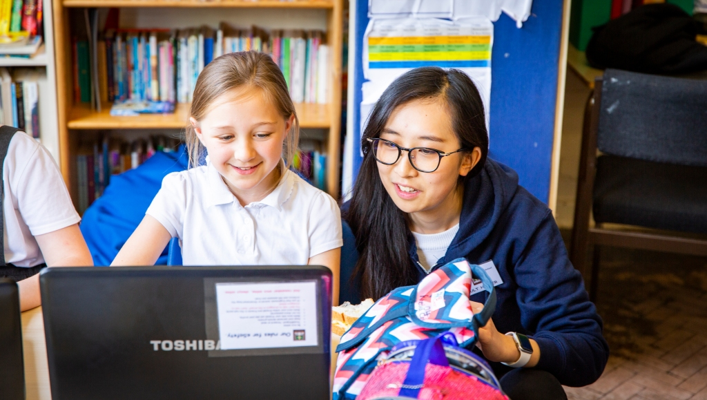 A young Code Club girl is sat at a desk smiling whilst looking at her laptop. Knelt down beside her is a female volunteer who is looking at the laptop and is smiling too.
