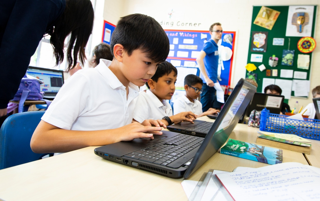 A primary school classroom, with a row of three boys are sat at a desk working on laptops.  Classroom displays can be seen in the background, along with a Code Club volunteer.