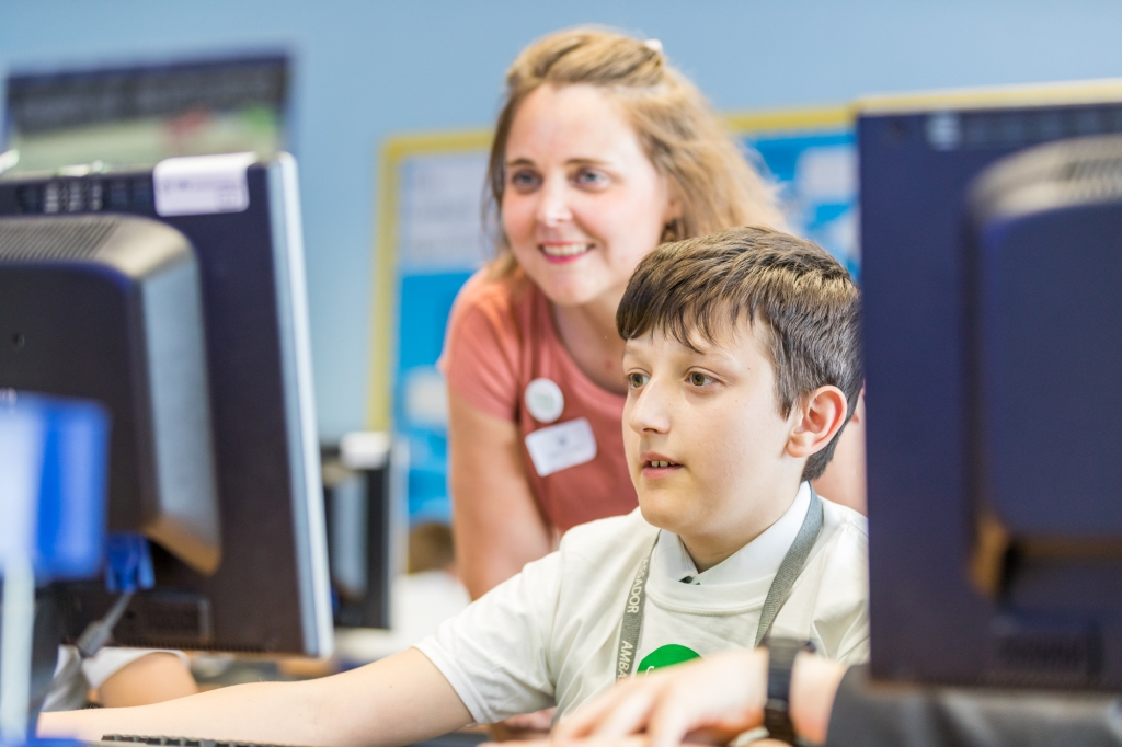 Young boy working at a computer with Zoe from Code Club smiling looking over his shoulder at the screen he is working on.
