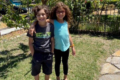 Ryaland and Logan are standing in the garden. Both smiling and Ryland has her arm over her brothers shoulder.