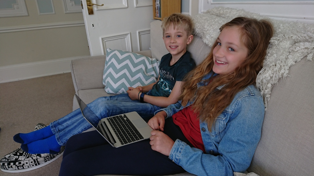 Freya and Lars sat on a sofa, Freya has a laptop on her lap. Both are smiling