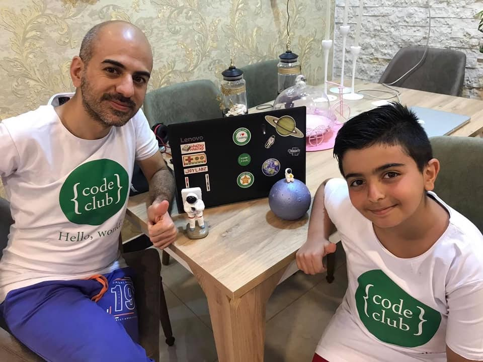 Mustafa is sat with his dad Ali at a table facing the camera. Both are wearing Code Club T-shirts and there is a laptop on the table.