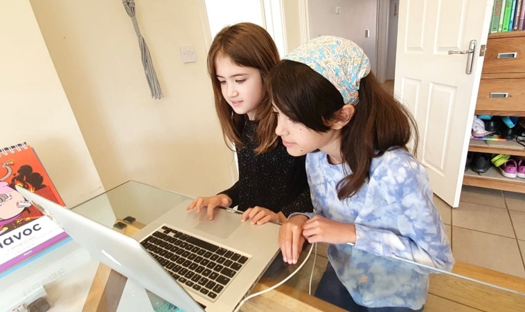Two young girls with long dark hair sat at the kitchen table, working together on a laptop