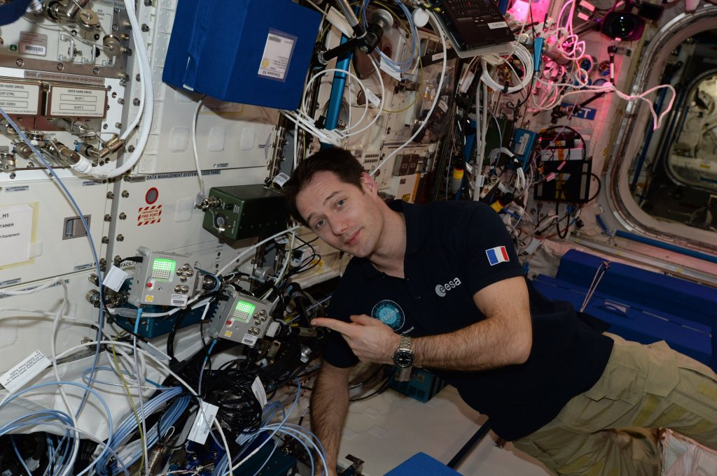An astronaut in onboard the International Space Station and is pointing towards the Astro Pi's.