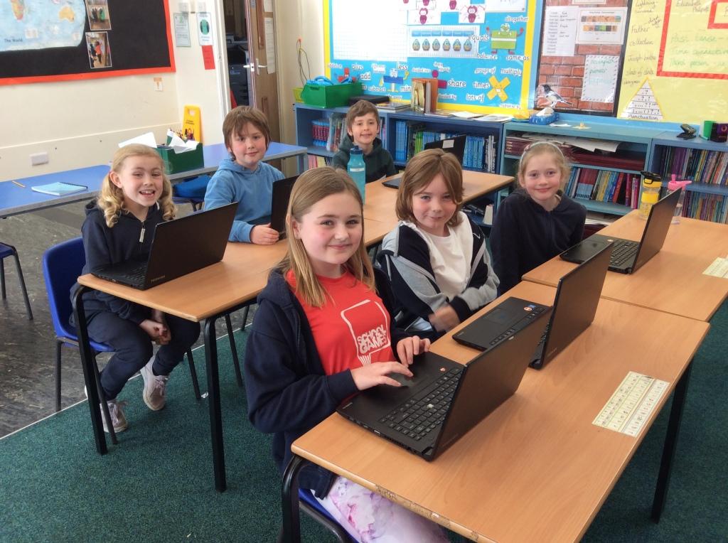 Six primary school children sat at their desks with laptops.