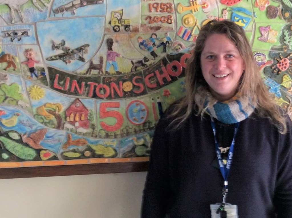 Female teacher Sophie Hudson stands in front of a wall mural