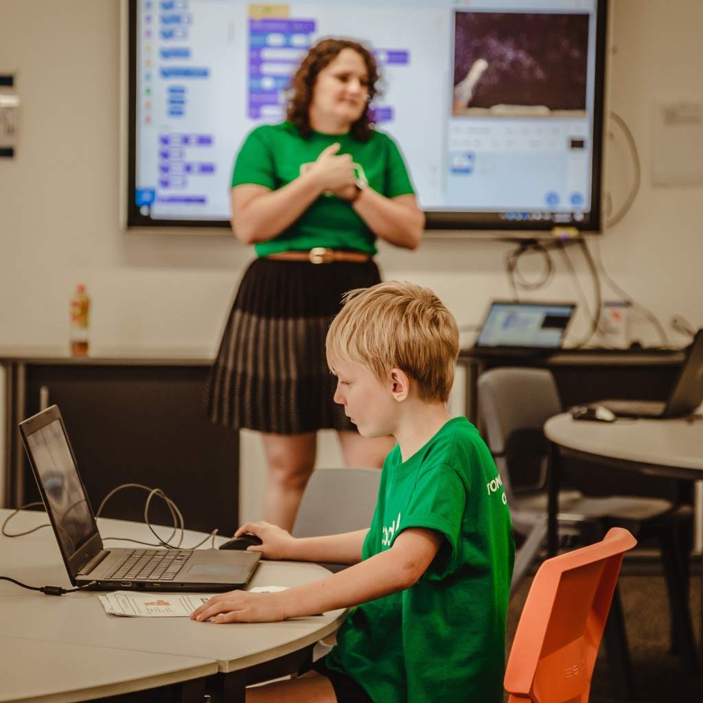 A young male coder is sat at a desk looking at a laptop.  A female educator is standing in the background